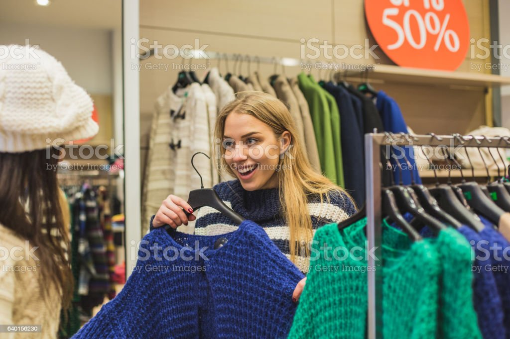 Helping girlfriend pick  clothes stock photo