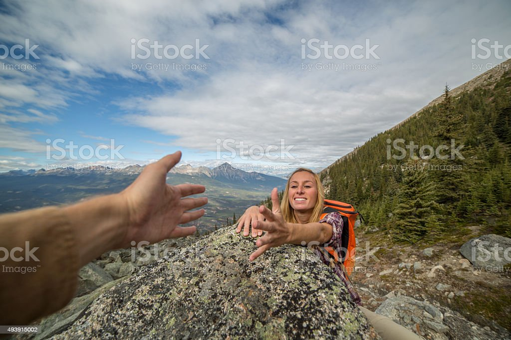 Helping hand at mountain top stock photo