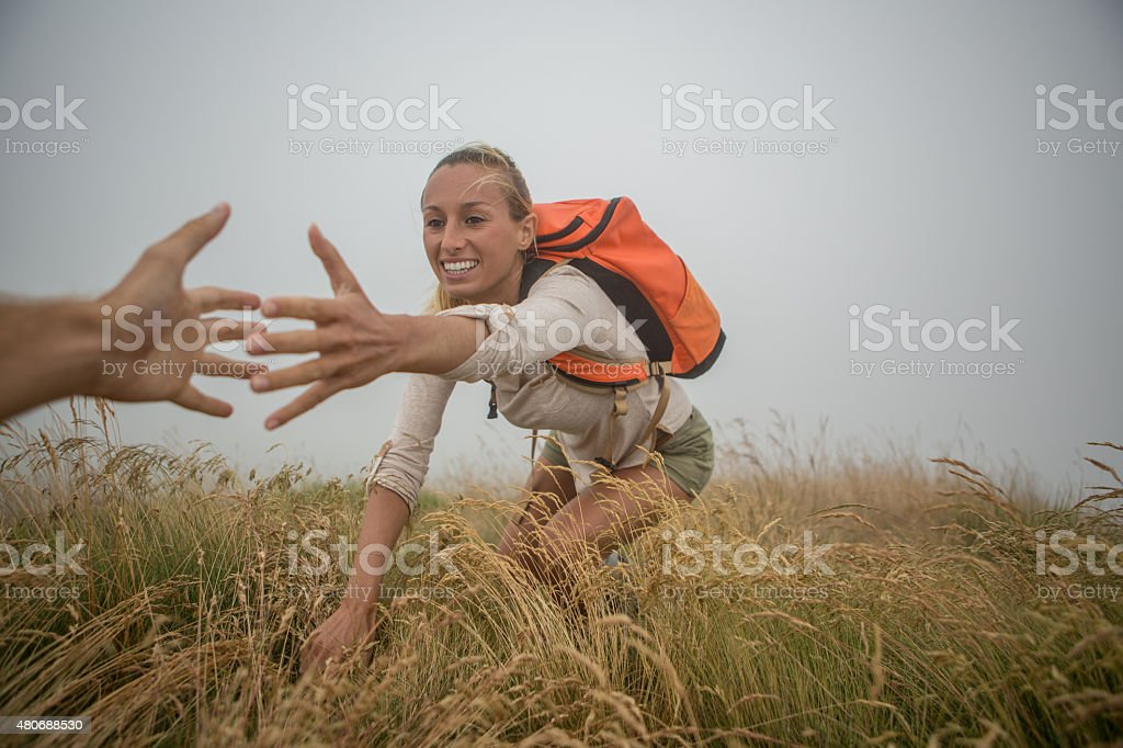 Helping hand at top of mountain stock photo