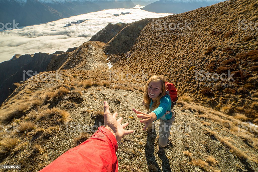 Helping hand between two climber - New Zealand stock photo