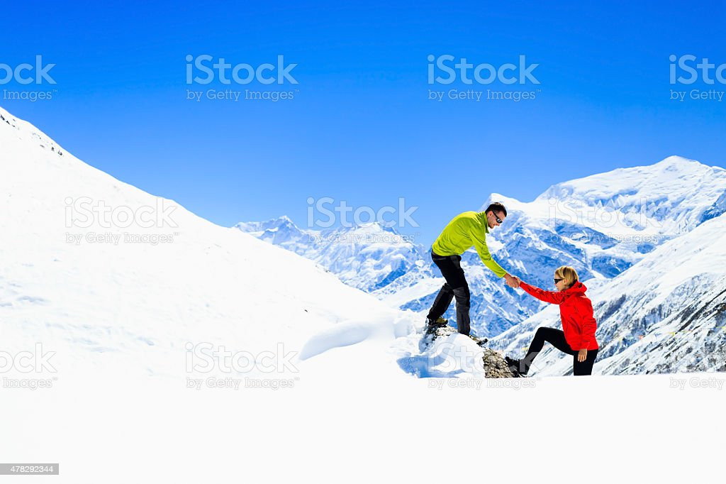 Helping hand couple hikers in mountains stock photo
