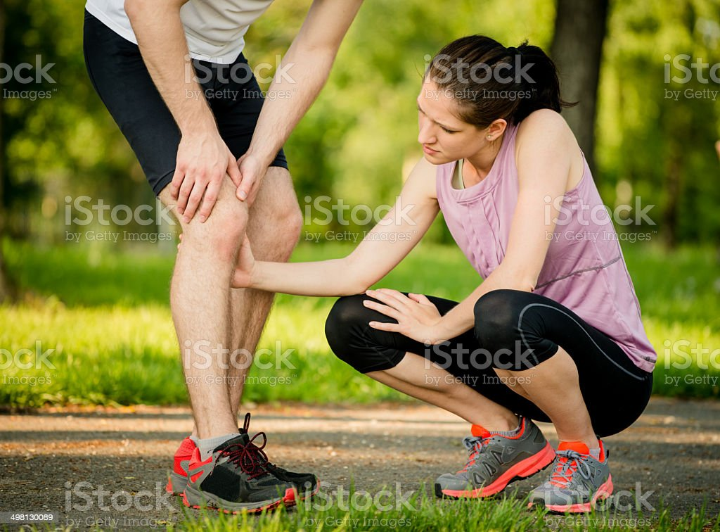 Helping hand - knee injury stock photo
