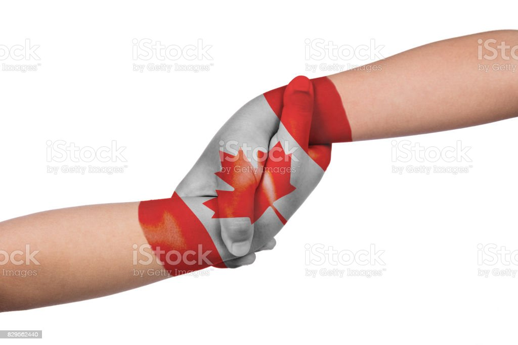 Helping hands of two children with Canada flag painted stock photo