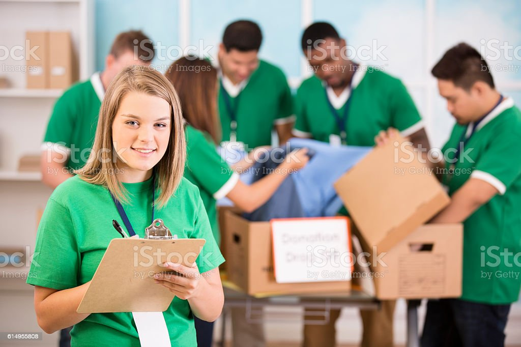 Helping Hands!  Young adult volunteers collect clothing donations. stock photo