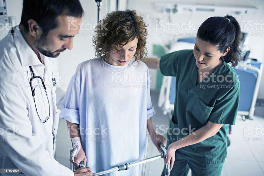 Helping patient use walker in hospital stock photo