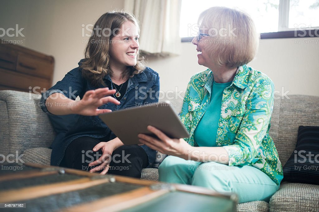 Helping Senior Woman With Technology stock photo