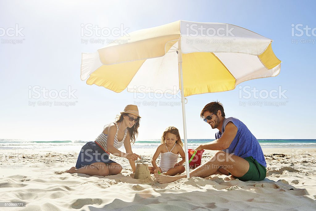 Helping their little girl build a sandcastle stock photo