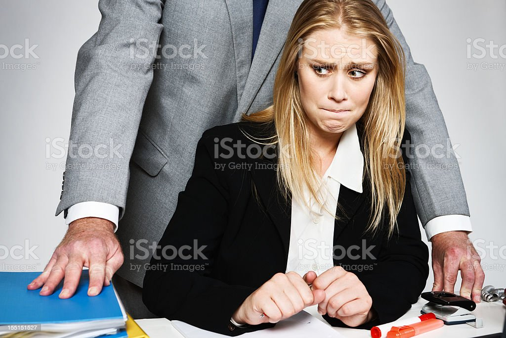 Helpless blonde businesswoman is harassed by threatening businessman stock photo
