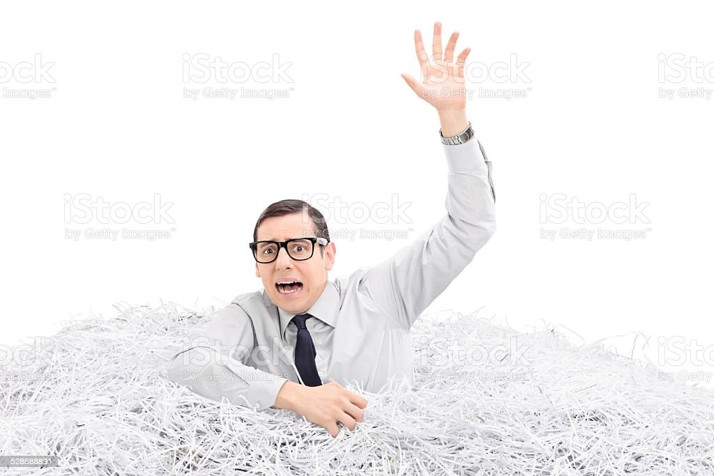 Helpless man drowning in a pile of shredded paper stock photo