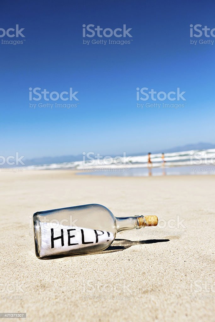 Helps says message in bottle washed up on shore royalty-free stock photo