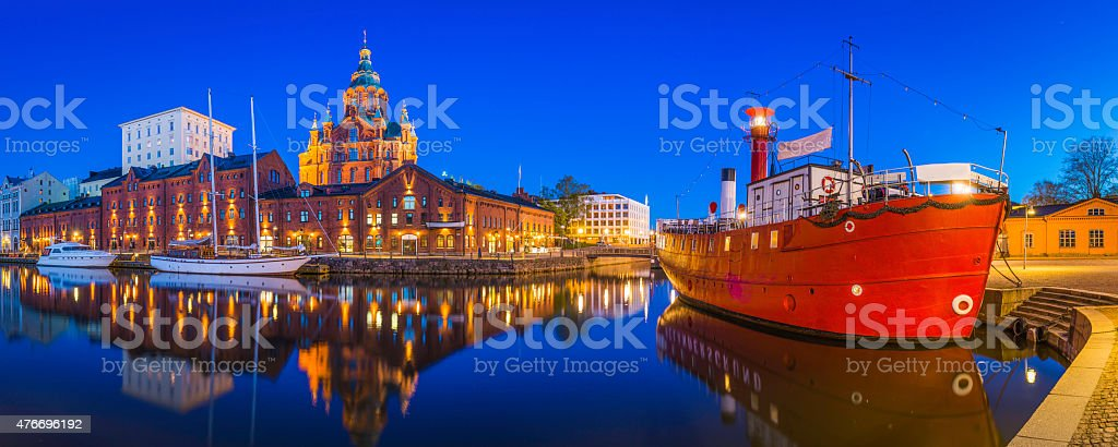 Helsinki Uspenski Cathedral overlooking tranquil waterfront harbour illuminated dusk Finland stock photo