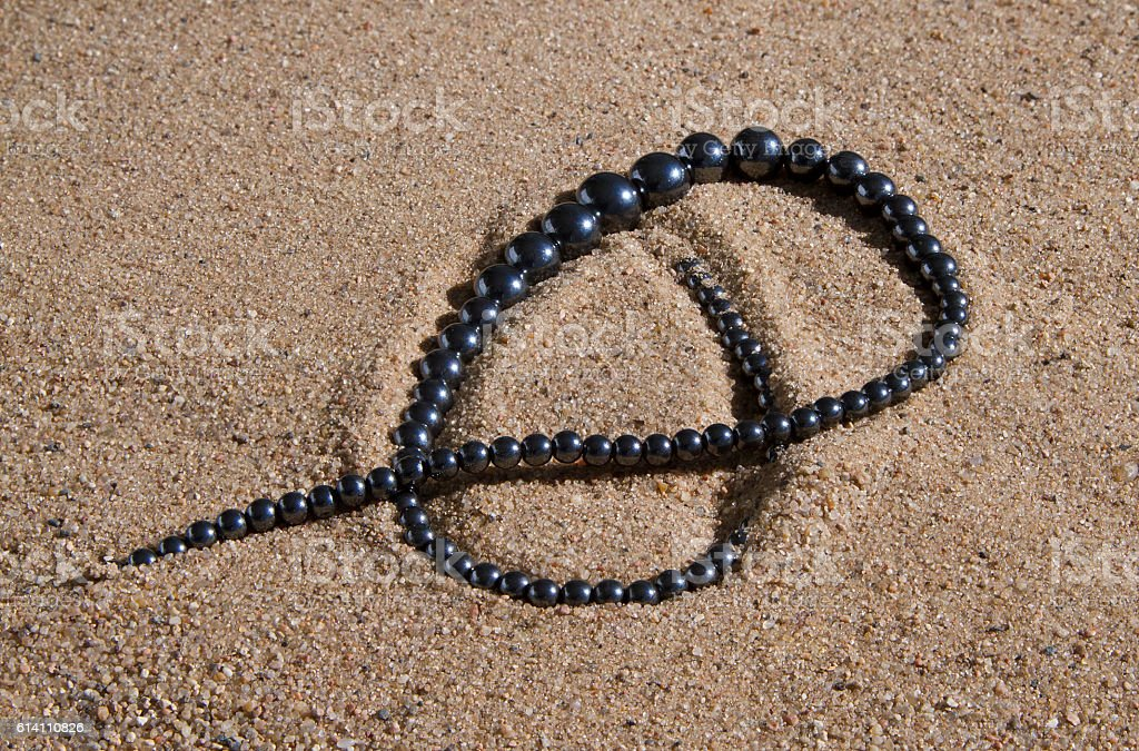 hematite beads lie on the sand stock photo