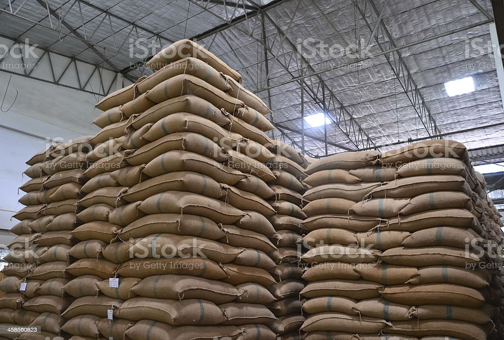 Hemp sacks stacked high in a large warehouse stock photo