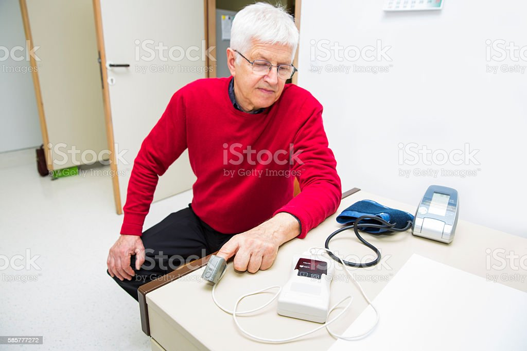 Hendheld pulse oxymeter.....senior patient testing oxygen saturation stock photo
