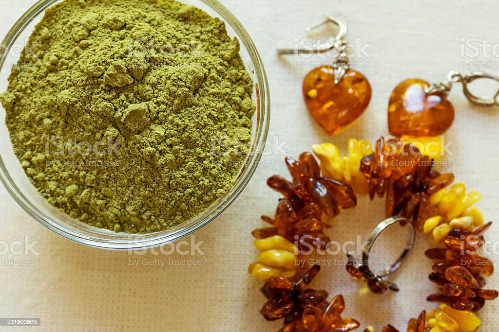 Henna powder. Still life with henna and amber jewelry. stock photo