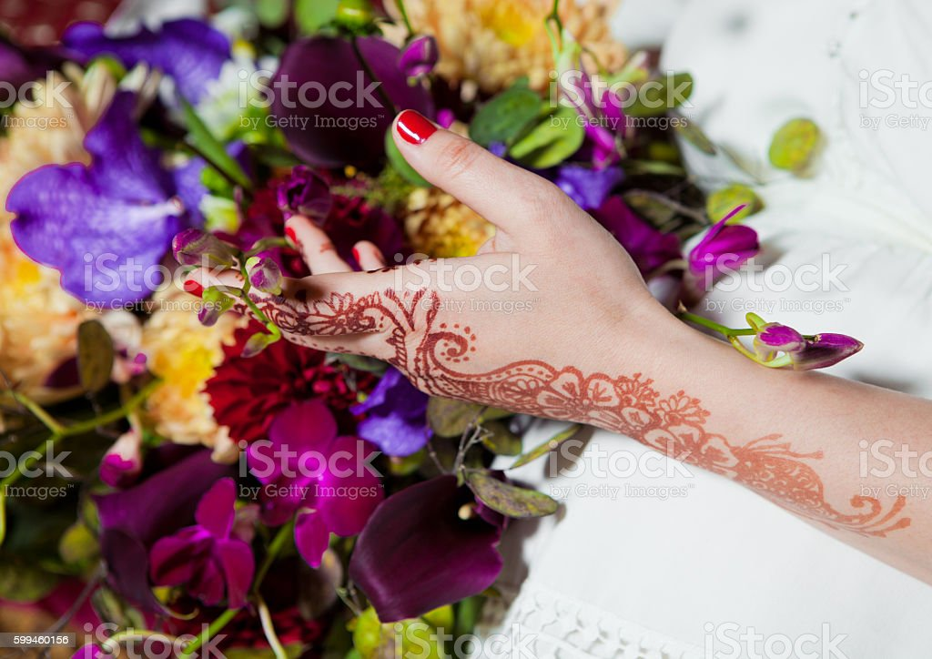 Henna tattoo on hands holding colorful flowers mix stock photo