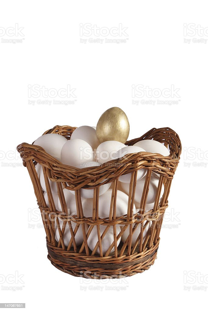 Hens eggs with gold one in a basket shot stock photo