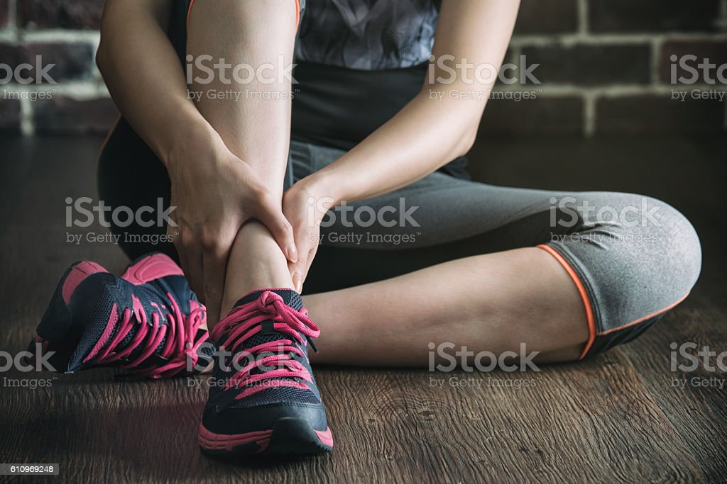 her ankle injured in gym fitness exercise training, healthy stock photo