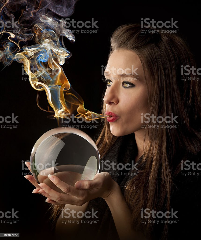Her Elemental Magic-Fortune Teller Blows Magic-Smoke Over Crystal Ball royalty-free stock photo