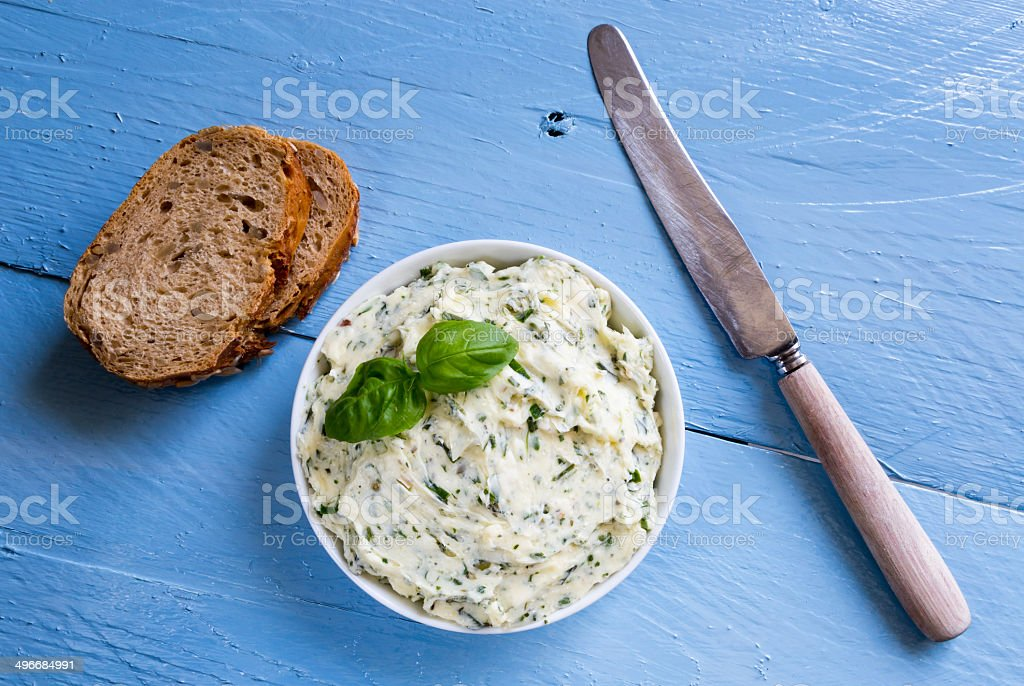 Herb butter in a bowl on blue wood stock photo