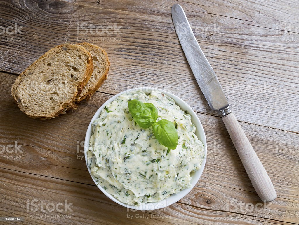 Herb butter in a bowl on wood stock photo