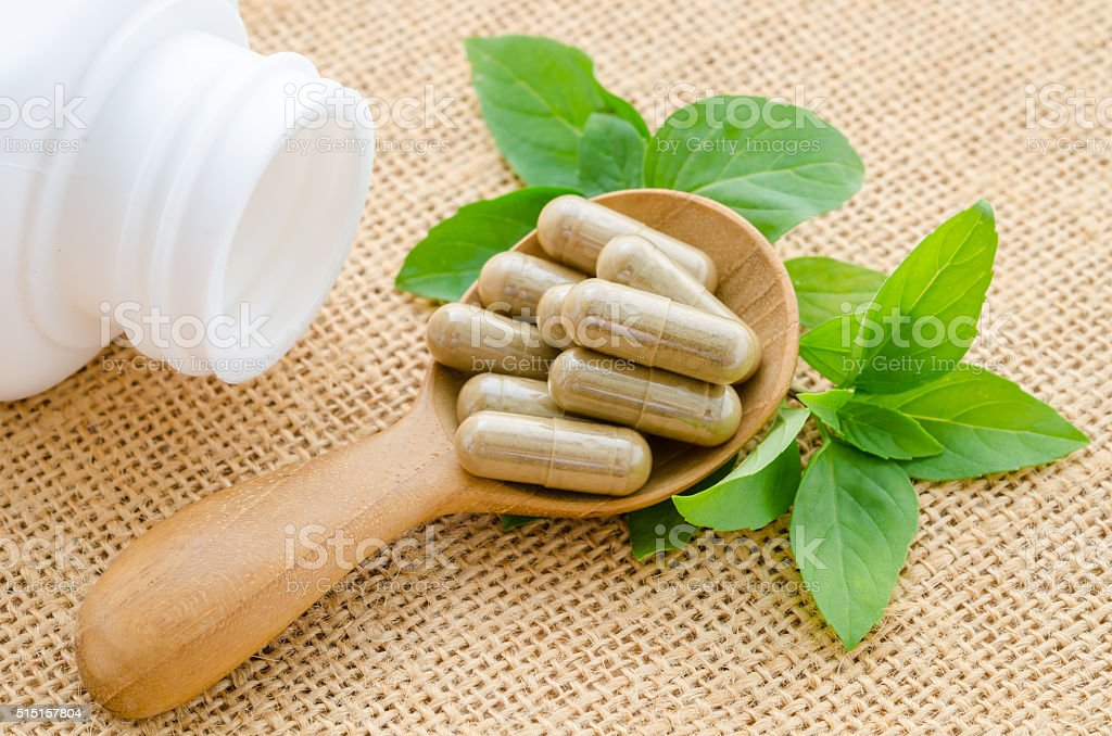 Herb capsule spilling out of a white bottle. stock photo