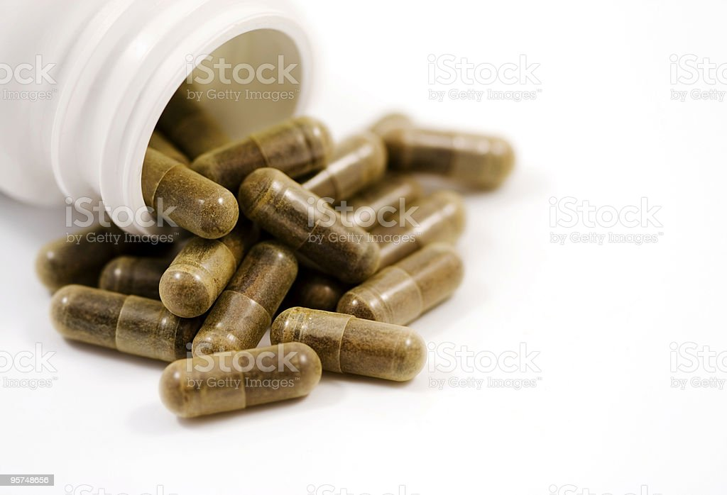 Herbal capsules spilling from bottle isolated on white royalty-free stock photo