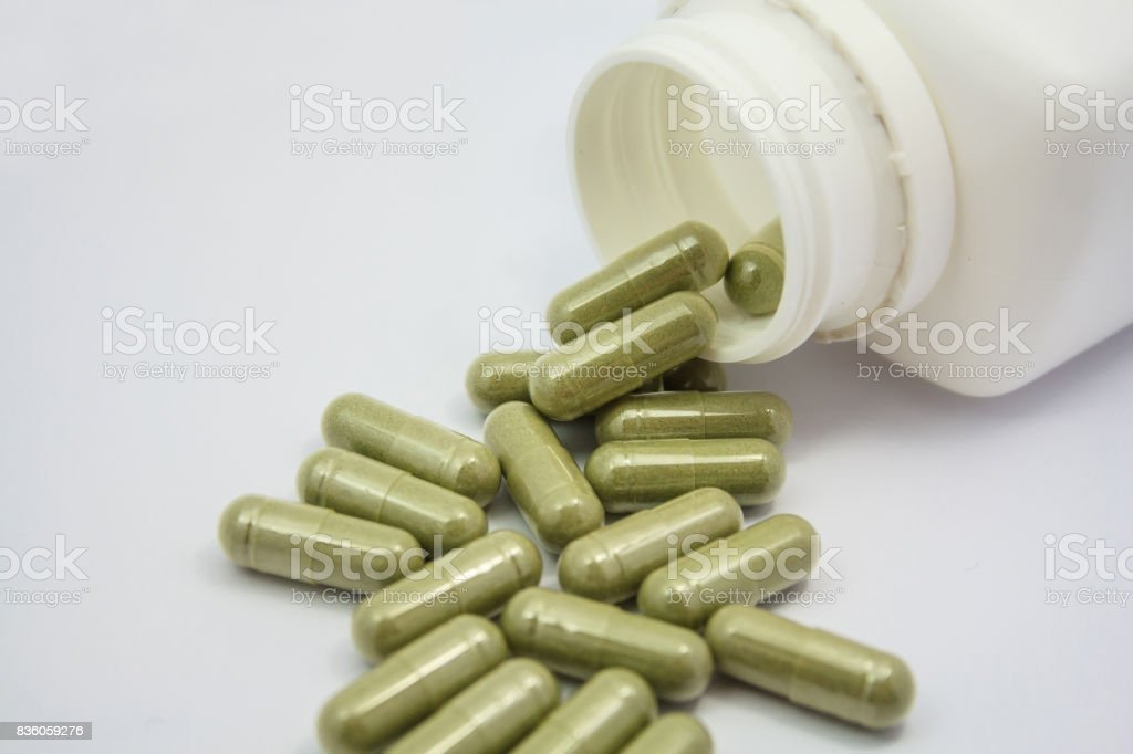 herbal capsules spilling out of a bottle stock photo