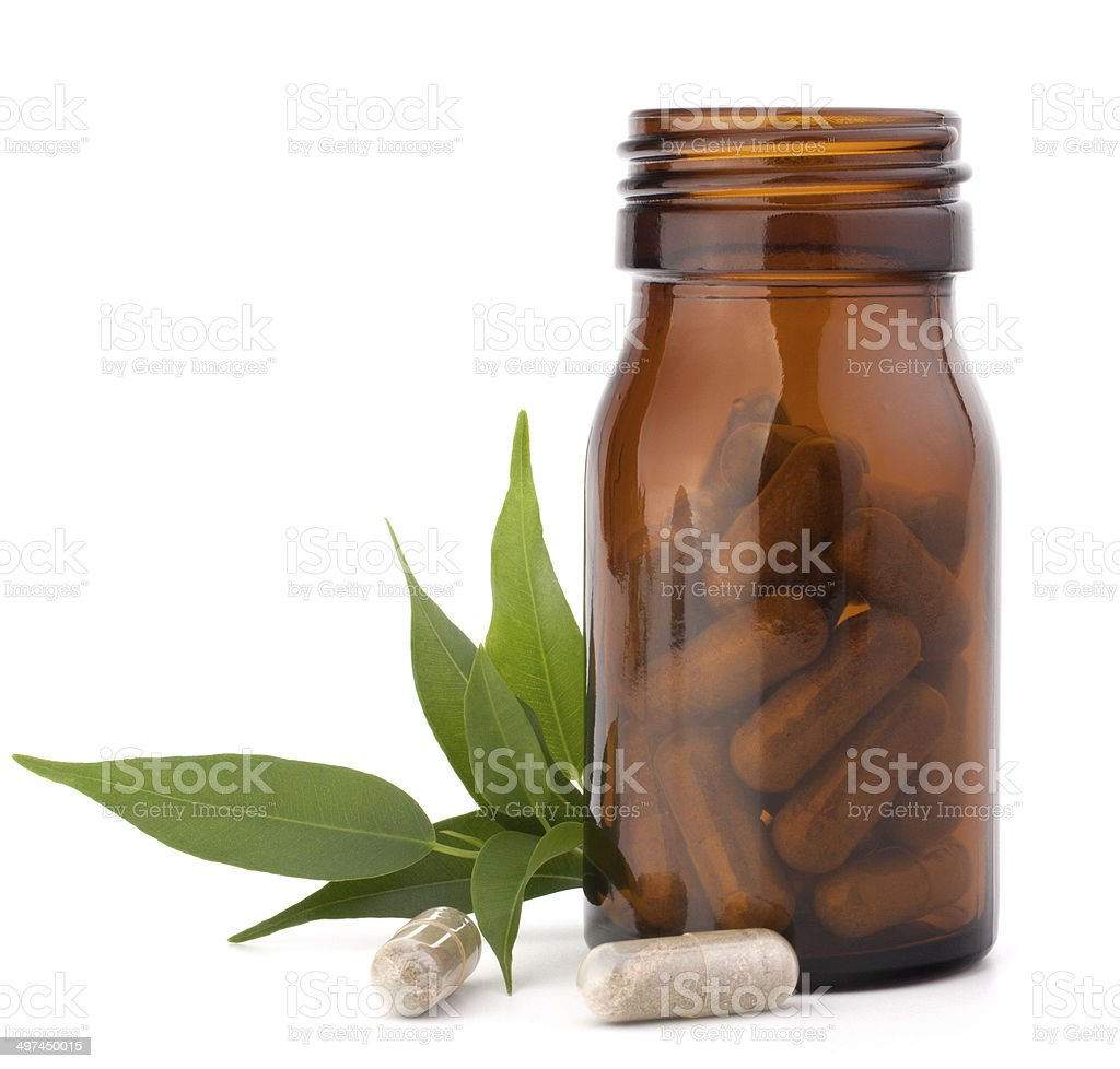 Herbal drug capsules in brown glass bottle. Alternative medicine stock photo
