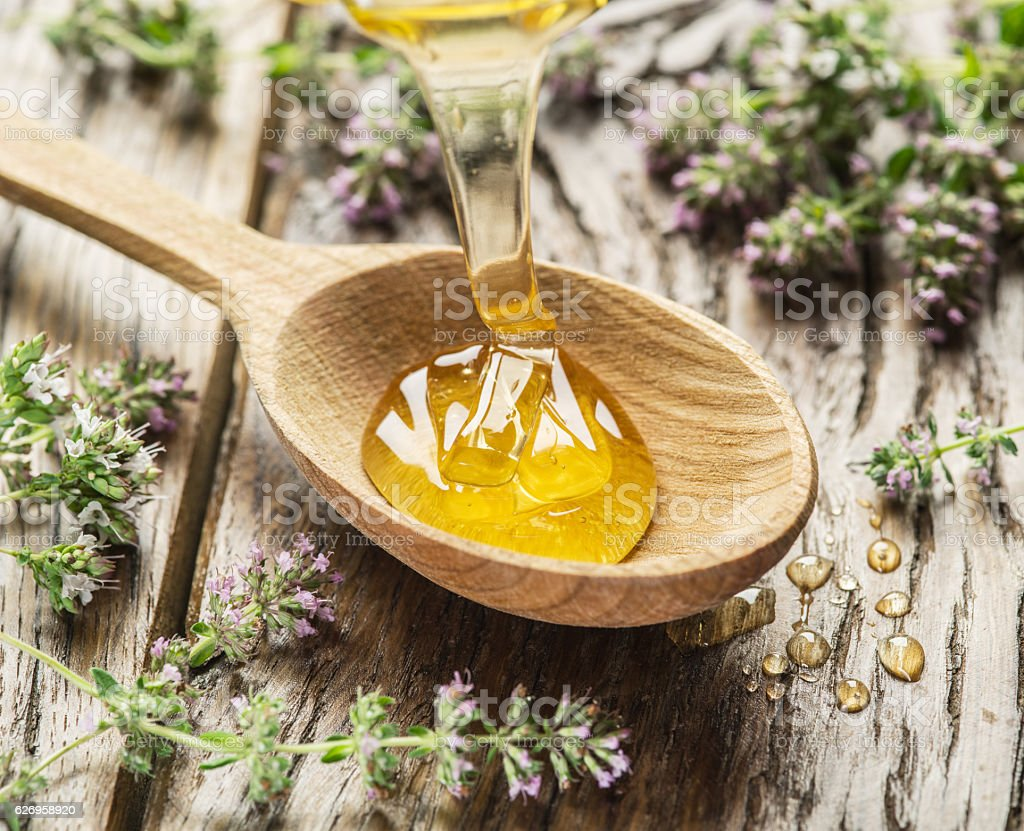 Herbal honey pouring into the wooden spoon. stock photo