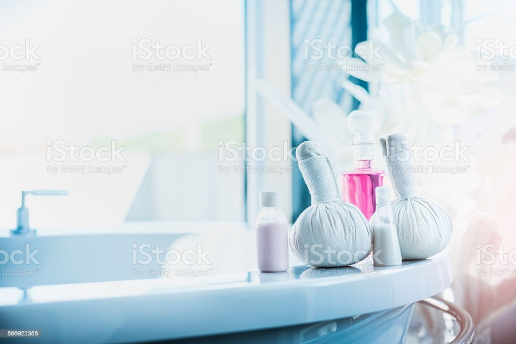 Herbal massage stamps , pink lotion bottle on light luxury bath stock photo