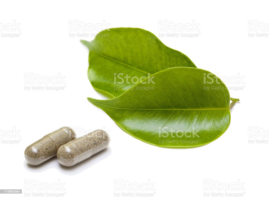 Herbal medicine capsules with green leaves royalty-free stock photo