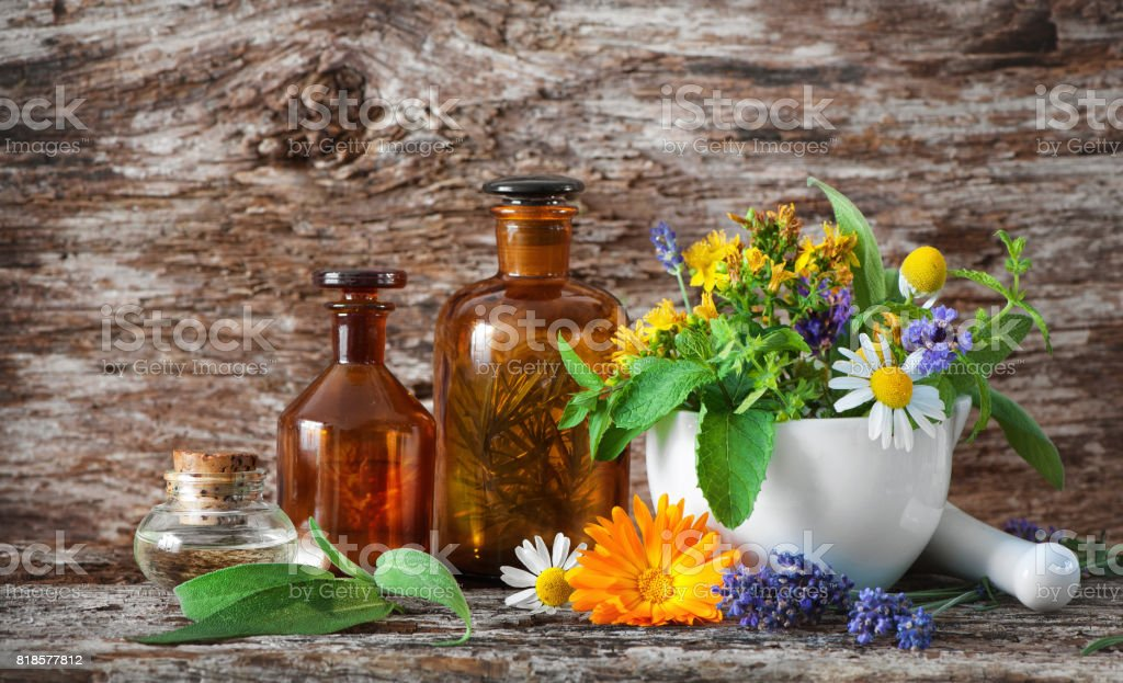 Tincture bottles and healing herbs in mortar on wooden table. Herbal...