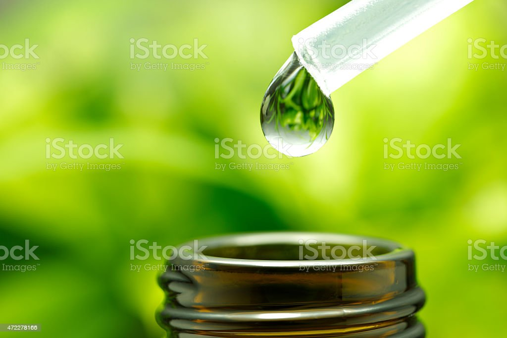Herbal oil droplet above amber glass jar stock photo