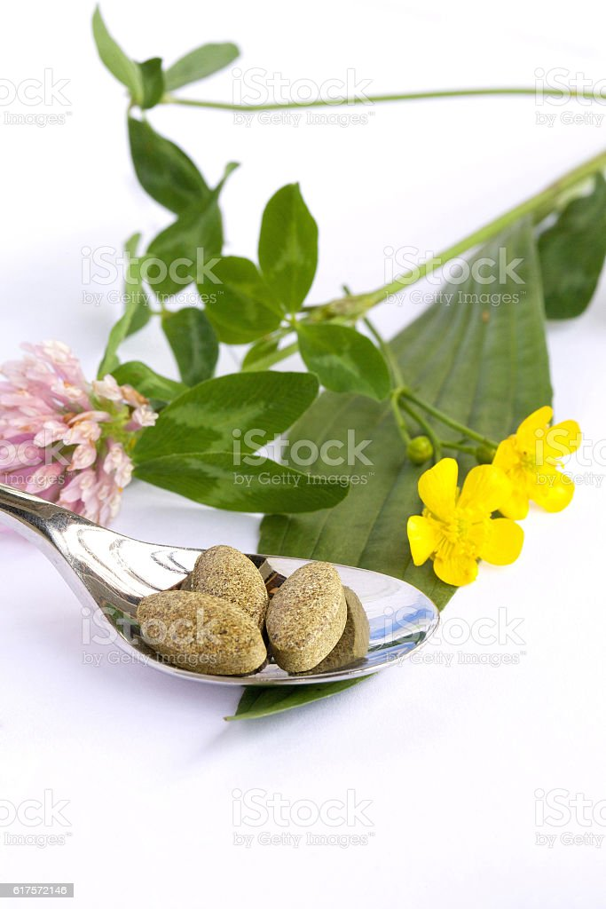 Herbal pills on a white background. Closeup stock photo