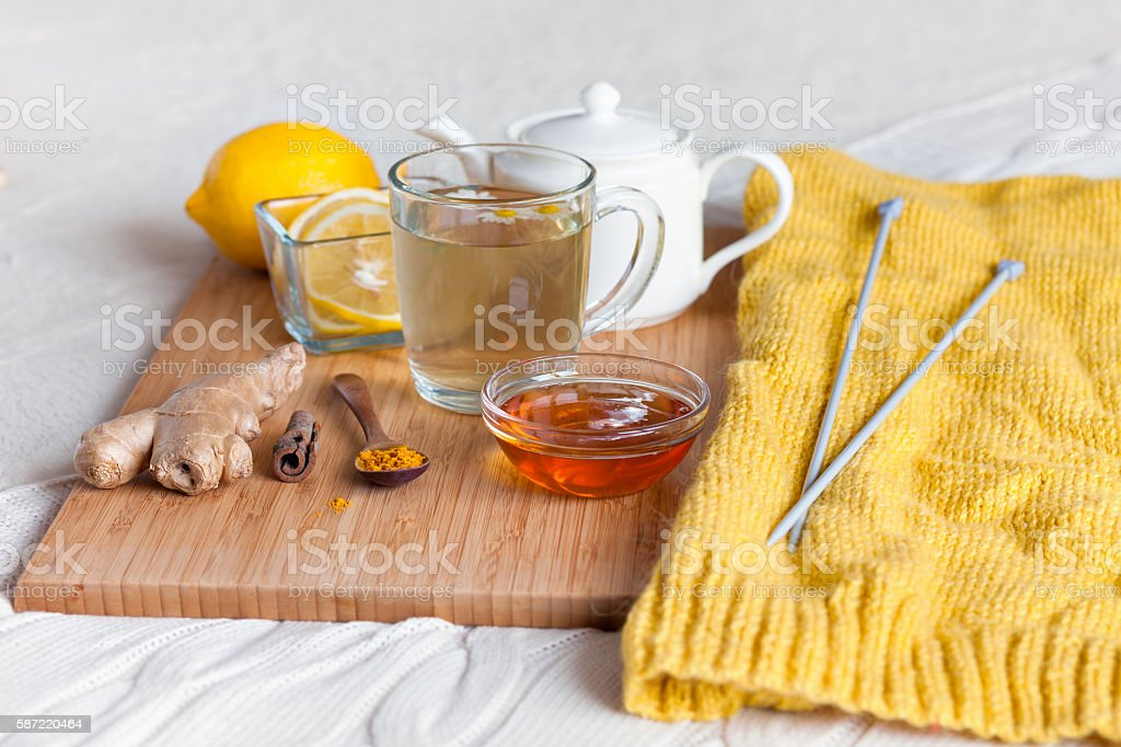 Herbal tea in glass cup with flowers of chamomile, turmeric stock photo