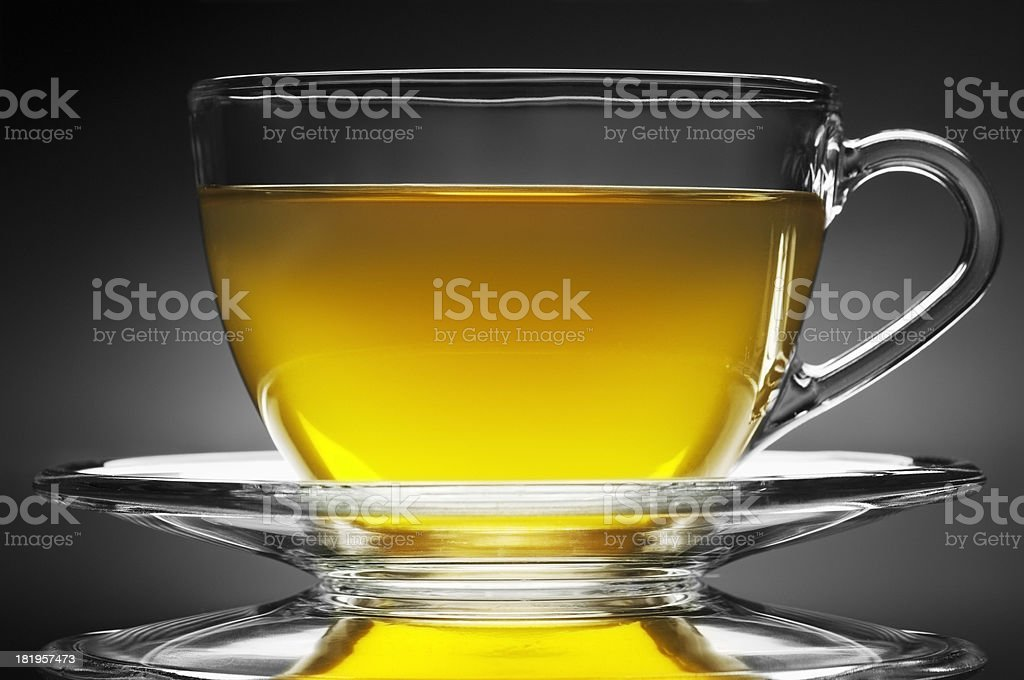 Herbal tea in glass cup with saucer on black background royalty-free stock photo