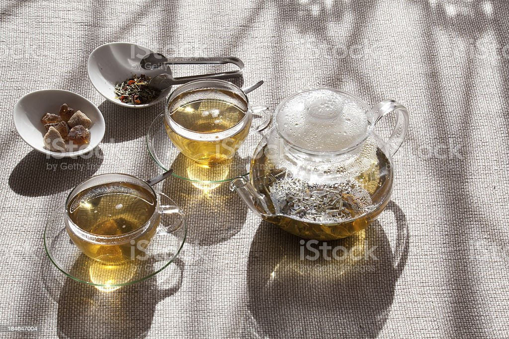 Herbal tea in two glass cups, transparent teapot and bowls royalty-free stock photo