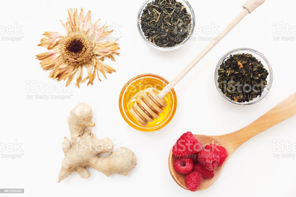 Herbal tea with honey, wild berry and flowers on white background. Flat lay, copy space stock photo