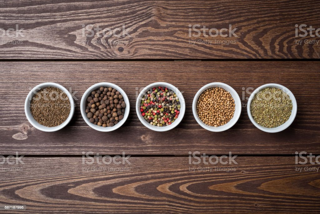 Herbs and spices in white bowls on wooden table stock photo