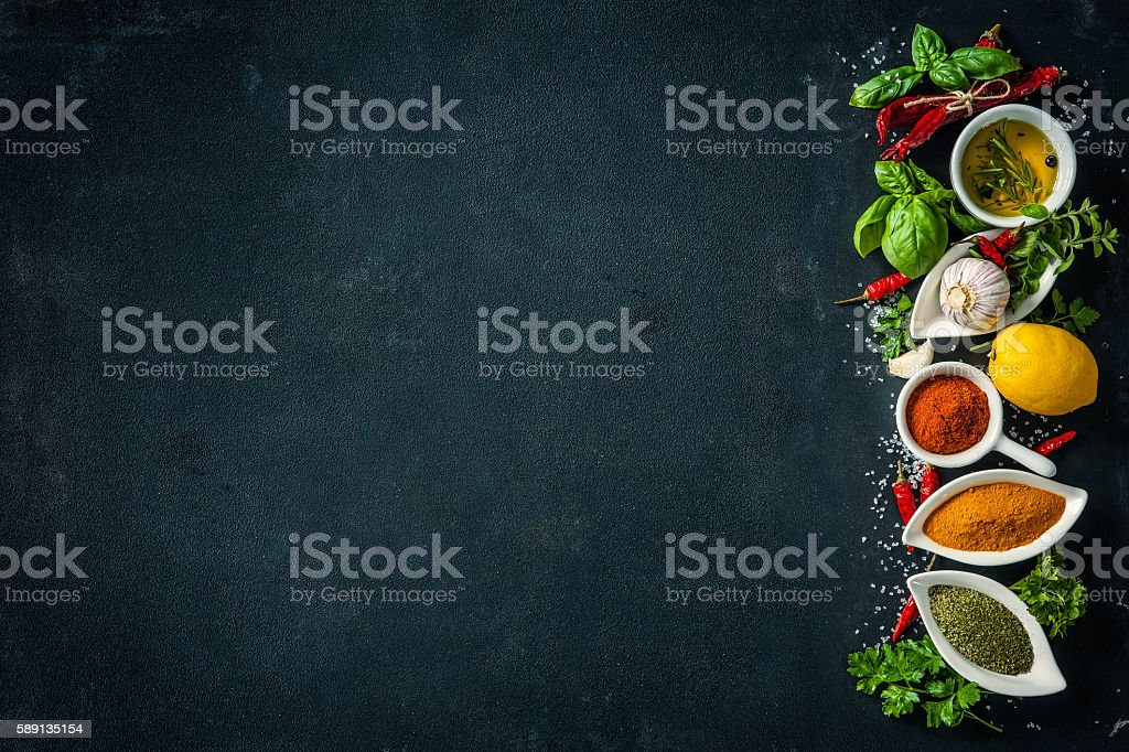 Herbs and spices over black stone background stock photo