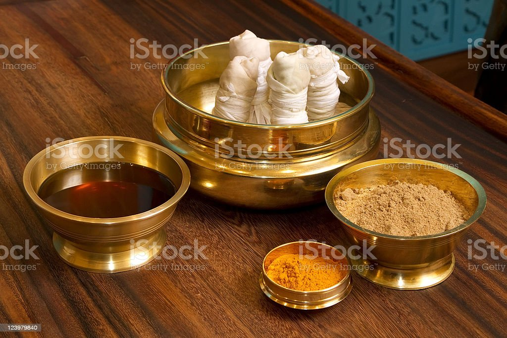 herbs powder and oil in bronze cups stock photo