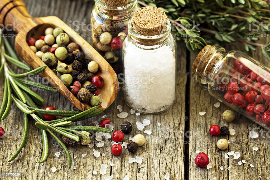 Herbs, salt and different kinds of pepper on wooden table stock photo