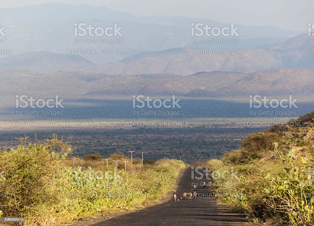 Herders on highway in the evening. Omo Valley. Ethiopia stock photo