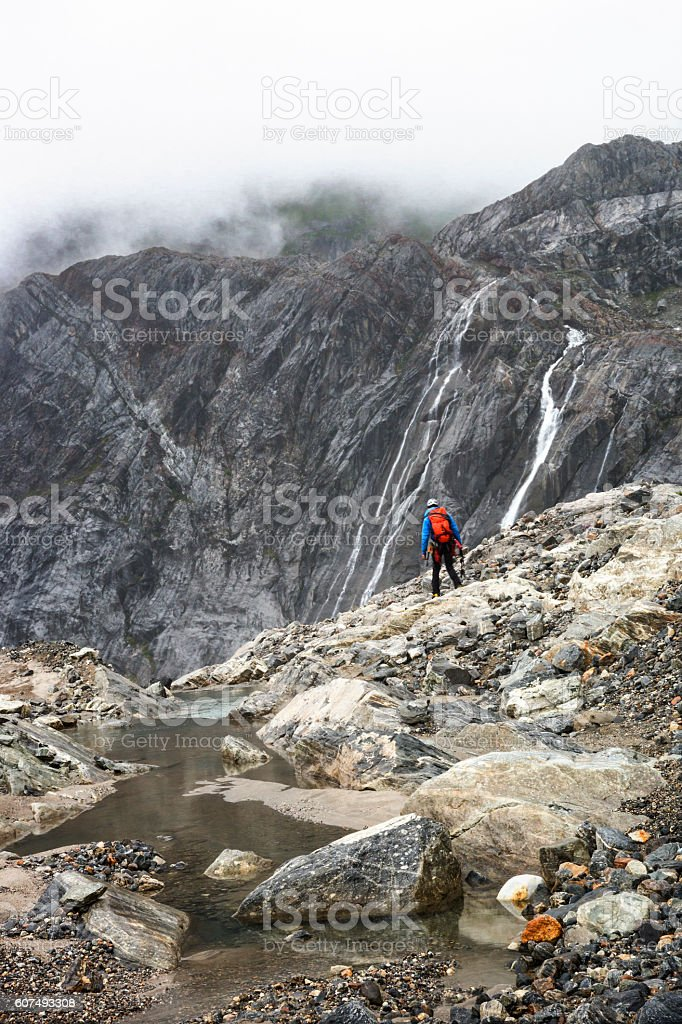 Hero shot of hiker in rocky glacier terrain stock photo