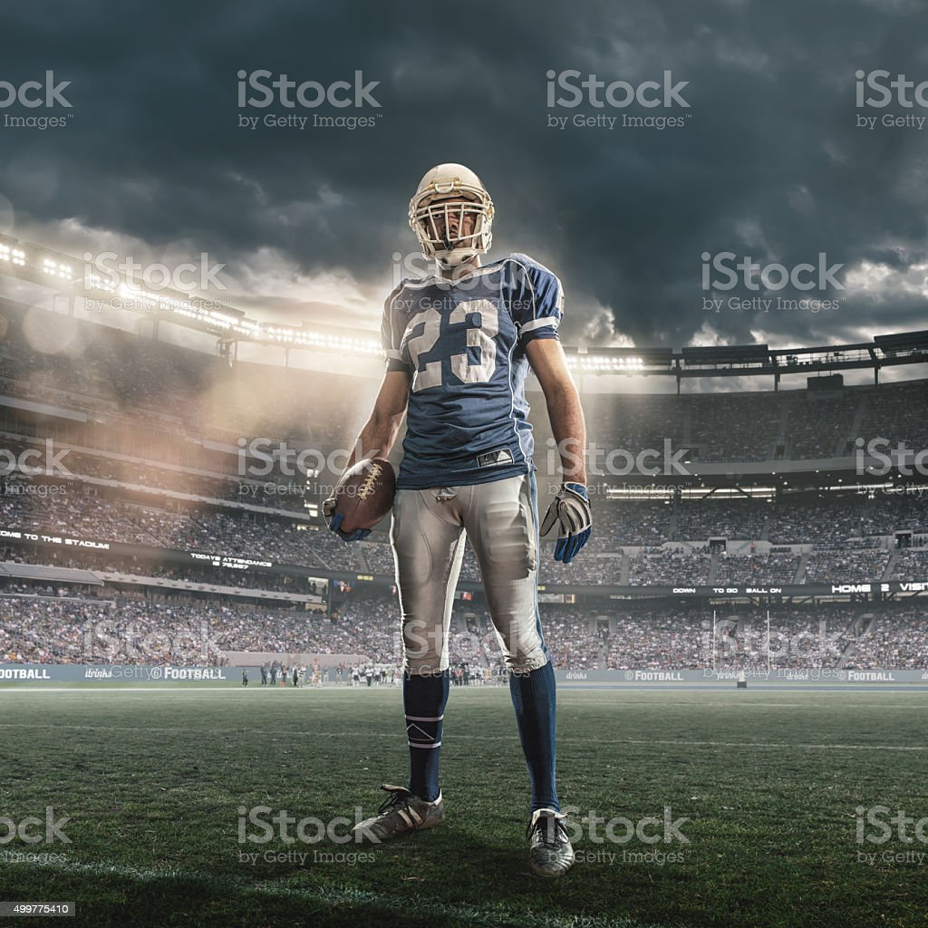 Heroic American Football Player Stadium With Ball In Floodlit Stadium stock photo