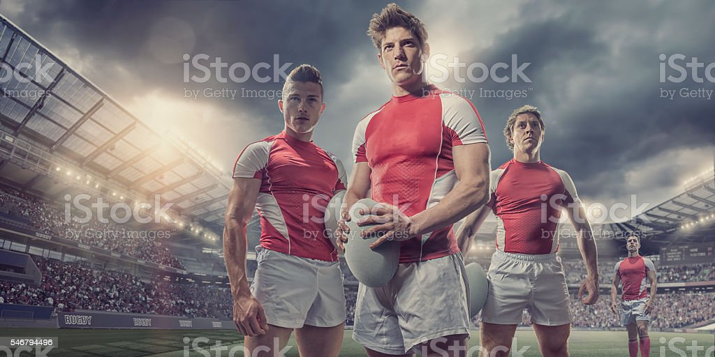 Heroic Rugby Players Standing With Ball On Pitch In Stadium stock photo