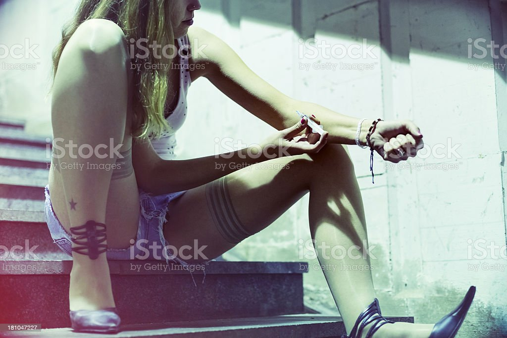 Heroine addict shooting up in dark street royalty-free stock photo