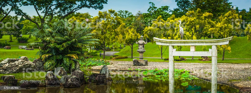 Heron perched on torri gate in park Japanese Gardens Singapore stock photo