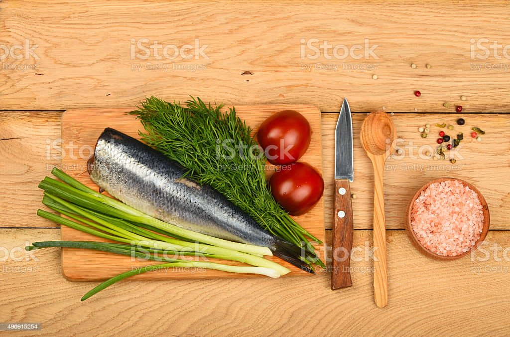 Herring double fillet with vegetables on wooden table royalty-free stock photo